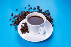 有咖啡五谷的浓咖啡杯子在蓝色背景的 库存图片