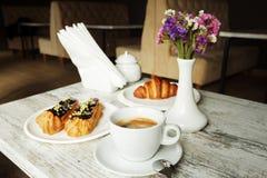 有咖啡小饼和新月形面包的白色板材与杯子新鲜的无奶咖啡 库存图片
