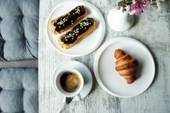 有咖啡小饼和新月形面包的白色板材与杯子新鲜的无奶咖啡 库存照片