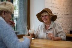 有咖啡微笑的资深妇女 免版税图库摄影