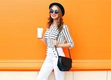 有咖啡杯佩带的时尚黑帽会议白色的俏丽的微笑的妇女气喘在五颜六色的桔子的提包传动器 免版税库存照片