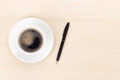 有咖啡杯和笔的办公桌 免版税库存图片