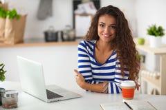 有咖啡杯和膝上型计算机的微笑的少妇 免版税库存图片