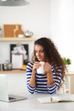 有咖啡杯和膝上型计算机的微笑的少妇 库存图片