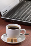 有咖啡杯和被打开的便携式计算机的,没有人民桌面,集中于咖啡 免版税库存图片