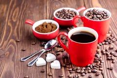有咖啡杯的两个杯子用在红色杯子附近的咖啡豆木背景咖啡豆 免版税库存照片