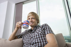 有咖啡杯的体贴的微笑的中间成人人在客厅在家 库存图片
