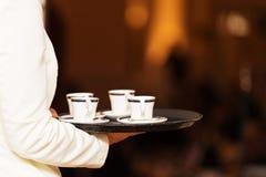 有咖啡杯的侍者运载的盘子在某一欢乐事件 图库摄影