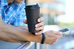 有咖啡杯的千福年的人举行智能手机 库存照片