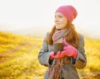 有咖啡杯的年轻俏丽的妇女在手上享受秋季的 免版税库存照片