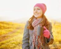有咖啡杯的年轻俏丽的妇女在手中享受秋季的 免版税图库摄影
