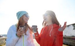 有咖啡杯的愉快的十几岁的女孩在街道上 免版税图库摄影
