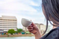 有咖啡杯的有些妇女在被弄脏的塔大厦 图库摄影