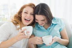 有咖啡杯的朋友在家享受交谈的 库存照片