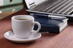 有咖啡杯的桌面,在背景,没有人民的被打开的便携式计算机、日志、平底锅和文件文件夹,集中于咖啡 免版税库存照片