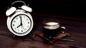 有咖啡杯的白色时钟8 O `时钟在木背景 免版税库存图片
