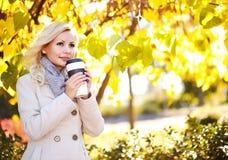 有咖啡杯的秋天妇女 秋天 美丽的白肤金发的女孩 免版税库存照片