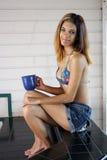 有咖啡杯的美丽的年轻西班牙妇女 免版税库存照片