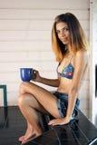 有咖啡杯的美丽的年轻西班牙妇女 免版税图库摄影