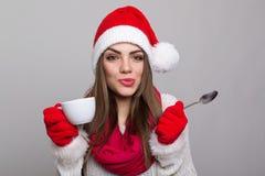 有咖啡杯的逗人喜爱的年轻圣诞老人女孩 库存图片