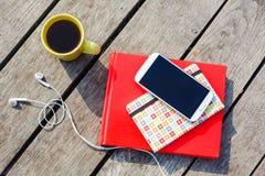 有咖啡杯的,智能手机,耳机工作地点,堆积了书 库存图片