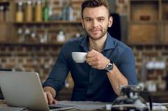 有咖啡杯的年轻人使用膝上型计算机和微笑对照相机 图库摄影