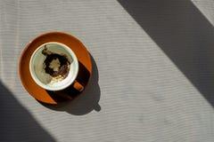有咖啡渣的布朗陶瓷杯子在茶碟 免版税库存图片