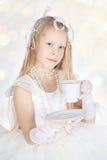 有咖啡的一点白肤金发的冬天女孩或茶 库存照片