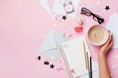 有咖啡的妇女手、macaron、办公用品和空的笔记本在桃红色淡色台式视图 平的位置样式 免版税库存照片
