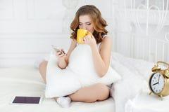 有咖啡的少妇和手机在床上早晨 免版税图库摄影
