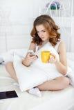 有咖啡的少妇和手机在床上早晨 库存照片