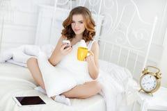 有咖啡的少妇和手机在床上早晨 图库摄影