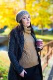 有咖啡的少妇在秋天公园 免版税库存照片