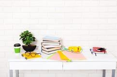 有咖啡的工作场所和教育材料在屋子里 砖墙和五颜六色的纸 选择聚焦 复制空间 嘲笑 库存照片