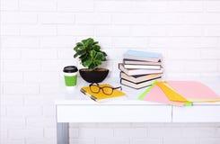 有咖啡的工作场所和教育材料在屋子里 砖墙 复制空间和选择聚焦 免版税库存照片