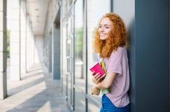 有咖啡的年轻微笑的红头发人学生女孩和书 免版税库存照片