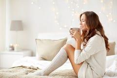 有咖啡的愉快的妇女在床上在家 图库摄影