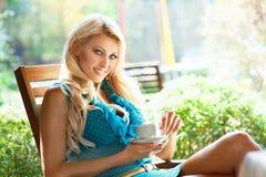 有咖啡的美丽的白肤金发的妇女在夏天咖啡馆的 免版税库存照片