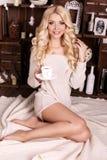 有咖啡的美丽的白肤金发的妇女,摆在圣诞树旁边 免版税库存图片
