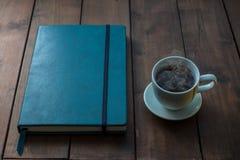 有咖啡的蓝色笔记本在木背景的 库存照片