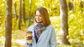 有咖啡的逗人喜爱的少妇在秋天公园 影视素材