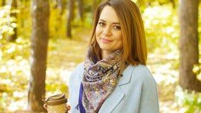 有咖啡的逗人喜爱的少妇在秋天公园 股票视频