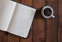 有咖啡的顶视图蓝色笔记本在木背景的 库存图片