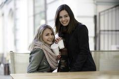 有咖啡盖帽的两个女孩  库存图片