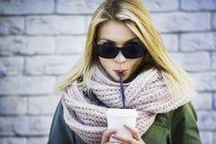有咖啡盖帽的凉快的女孩  库存图片