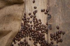 有咖啡豆和一杯咖啡的黑板在自然棕色木头的 免版税库存照片