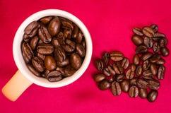 有咖啡豆心脏上面的黄色咖啡杯 免版税图库摄影