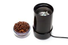 有咖啡豆电研磨机的杯 免版税库存图片