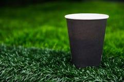 有咖啡费用的纸杯在绿草 免版税图库摄影