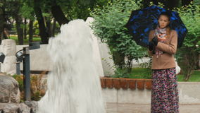 有哀伤的眼睛的一个美丽的女孩在雨中站立在城市公园,在喷泉附近